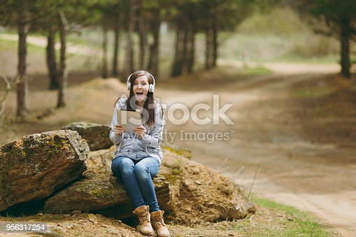 862602714istockphoto Young shocked overjoyed woman in casual clothes with headphones sitting on stone using tablet pc computer in city park or forest on green blurred background. Student lifestyle, leisure concept. 956317254