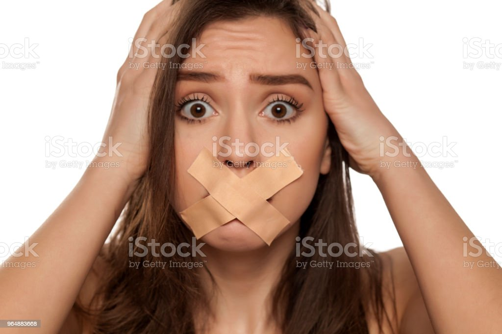 Young shocked woman with taped mouth on white background royalty-free stock photo