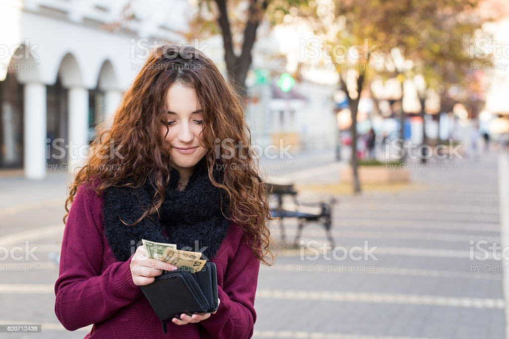 young shopper woman taking out money from wallet on street stock photo