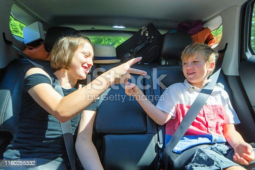 istock Young siblings playing in packed car on a road trip 1160255332