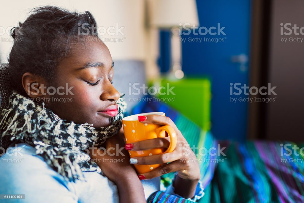 Young sick African woman in bed stock photo