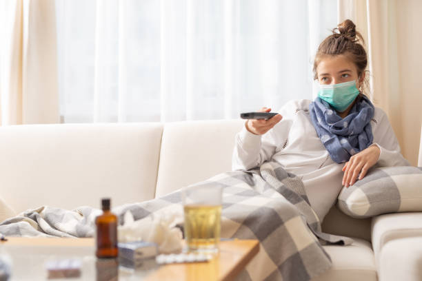 Young sick girl sitting on a sofa at home wathing tv. She has coronavirus pneumonia and she wears safety breathing protective mask to protect herself and others from sickness. stock photo