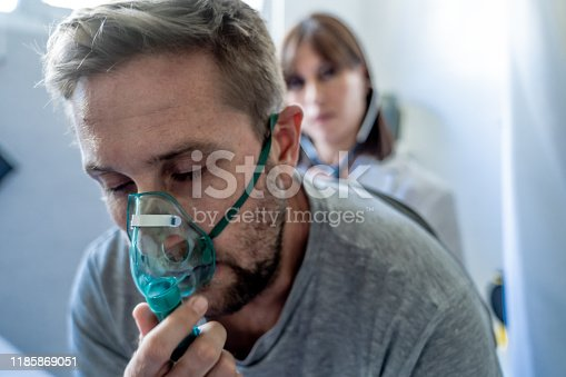 Young sick man patient with Oxygen Mask while female doctor listens his chest with stethoscope in hospital emergency room. In Smoking, respiratory diseases and Health care anti tobacco advertising campaign.