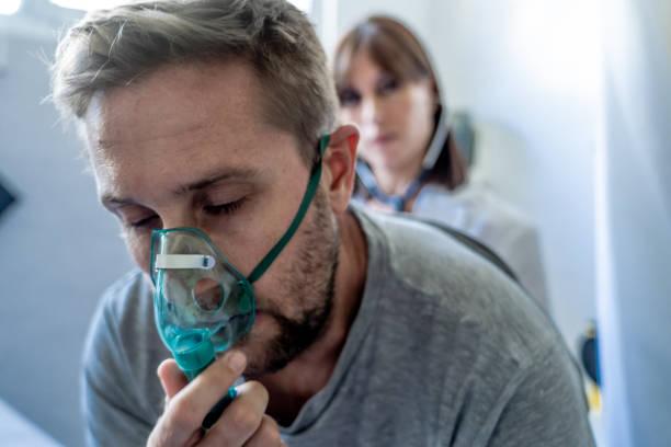 Junge kranke Mann Patient mit Sauerstoffmaske, während Ärztin hört seine Brust mit Stethoskop in Krankenhaus Notaufnahme. In der Kampagne Rauchen, Atemwegserkrankungen und Gesundheitsschutz anti Tabak. – Foto