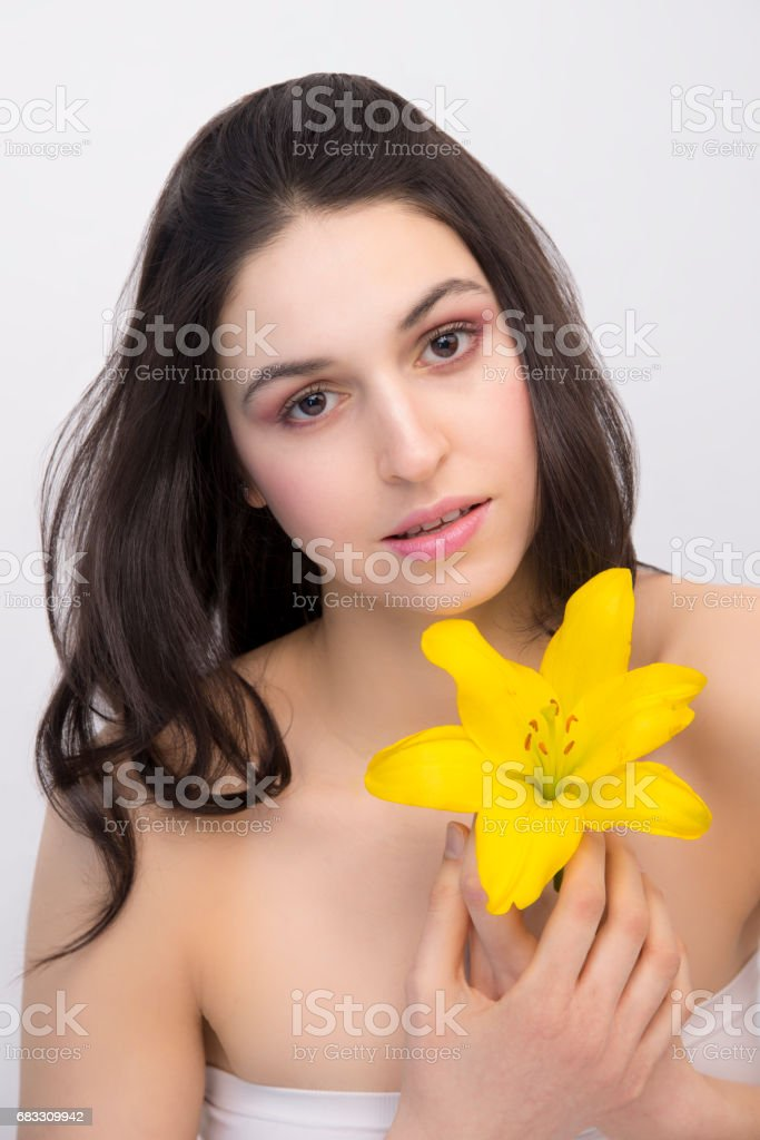 Young silky-skinned brunette woman posing with a yellow flower royalty free stockfoto