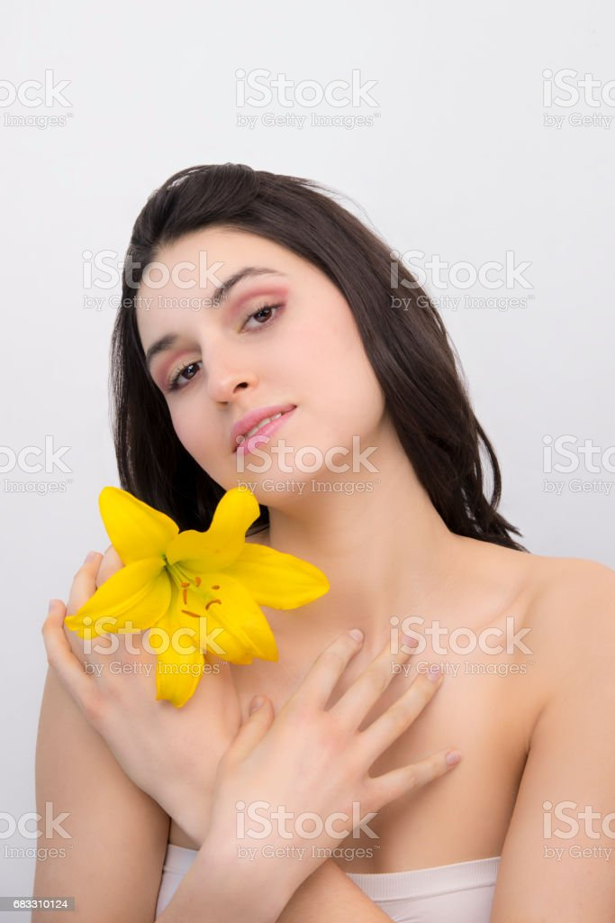Young silky-skinned brunette woman posing with a yellow flower zbiór zdjęć royalty-free