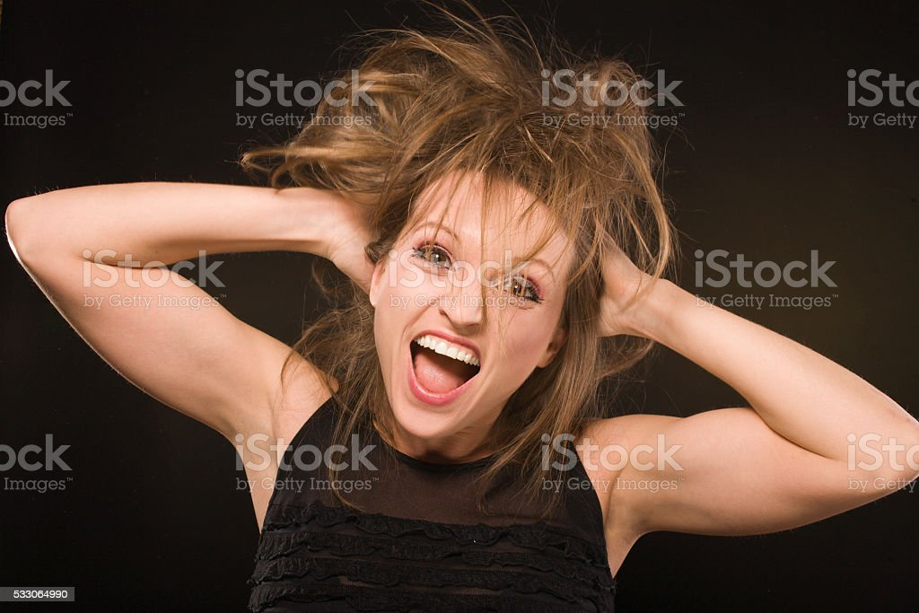 young silly crazy girl with messed hair making stupid faces stock photo
