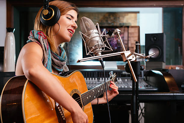 Young singer Young woman with guitar recording a song in the studio singer stock pictures, royalty-free photos & images