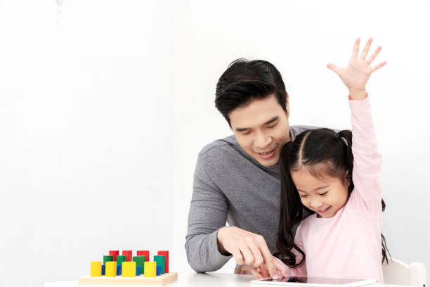 young single dad play smart gadget and have fun with daughter sitting on kid desk table with colorful block toy beside copy space on isolated white background. home school or preschool kids concept. - two students together asian foto e immagini stock