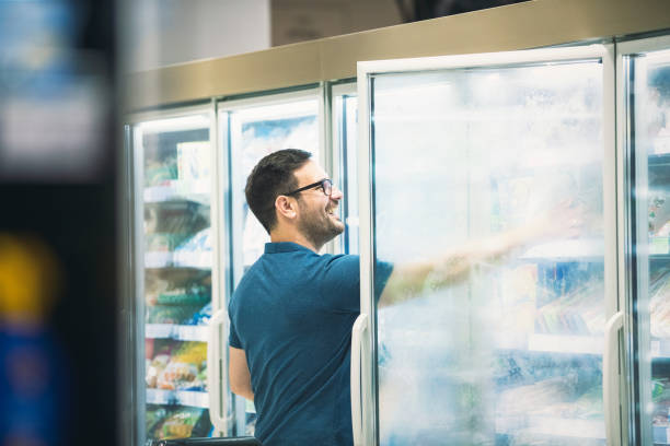 Young single man buying groceries at the supermarket Young single man buying groceries at the supermarket snack aisle stock pictures, royalty-free photos & images