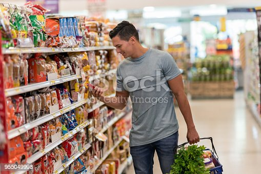 Young single man buying groceries at the supermarket reading the label of a product looking very happy and smiling
