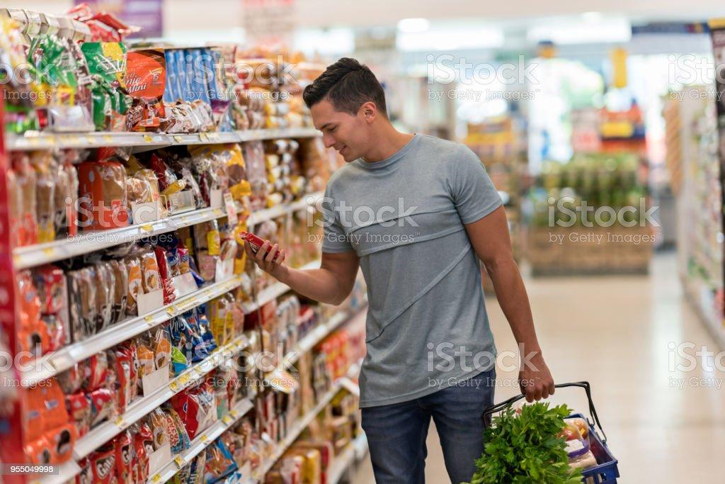 Junge alleinstehende Mann Kauf von Lebensmitteln im Supermarkt lesen das Etikett eines Produkts schauen sehr glücklich – Foto