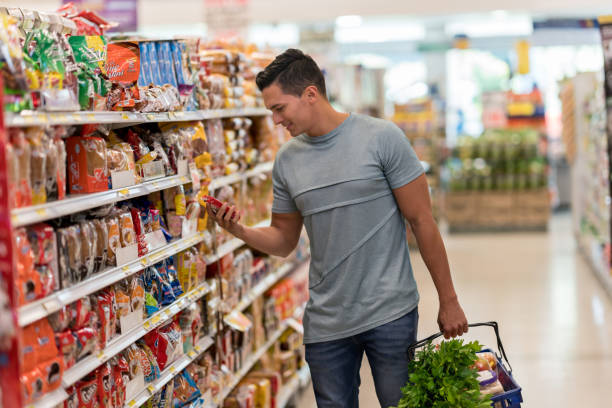 Young single man buying groceries at the supermarket reading the label of a product looking very happy stock photo