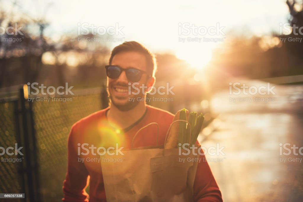 Young single man with groceries bag in his hands stock photo