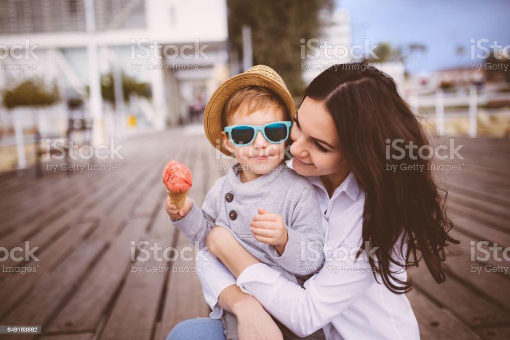 Young single mum hugging cute son who eats ice cream stock photo