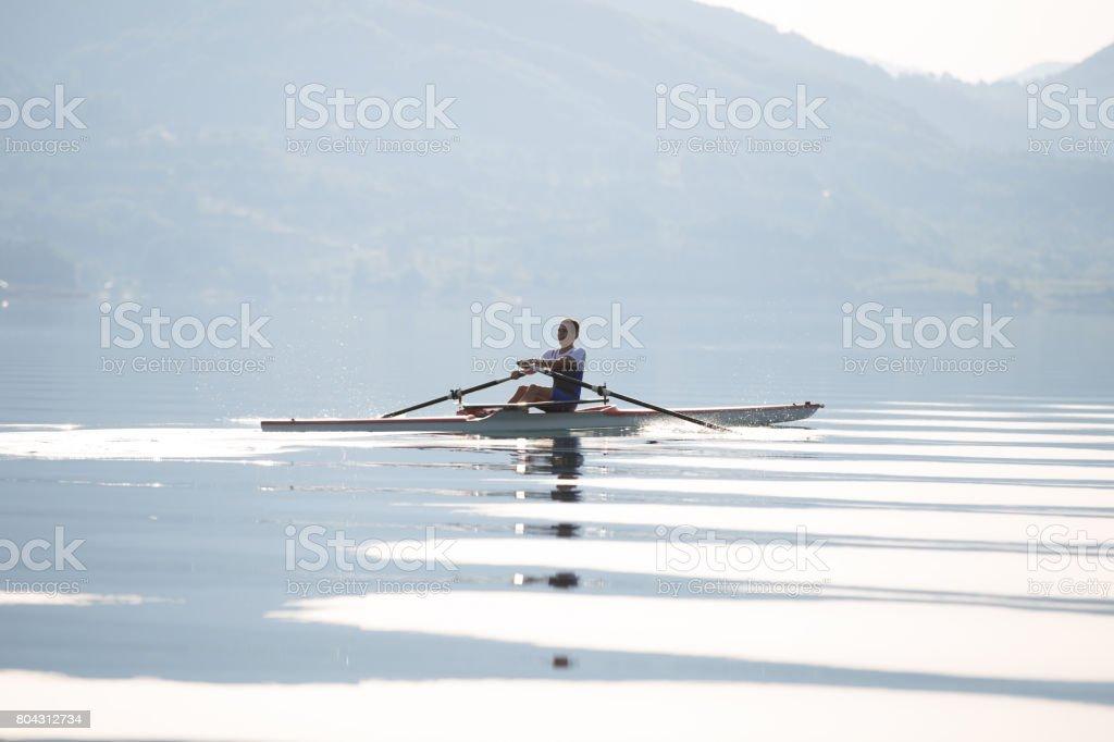 Ein junger einzelner Scull Rudern Konkurrent Paddel auf dem ruhigen See - Lizenzfrei Abheben - Aktivität Stock-Foto