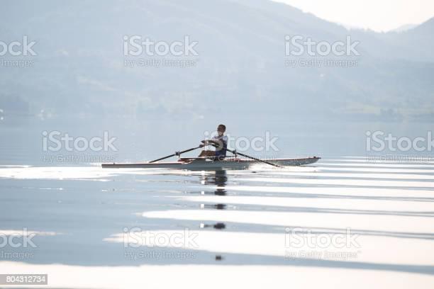 Ein Junger Einzelner Scull Rudern Konkurrent Paddel Auf Dem Ruhigen See Stockfoto und mehr Bilder von Abheben - Aktivität