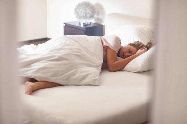Young single woman in bed at home in the morning stock photo