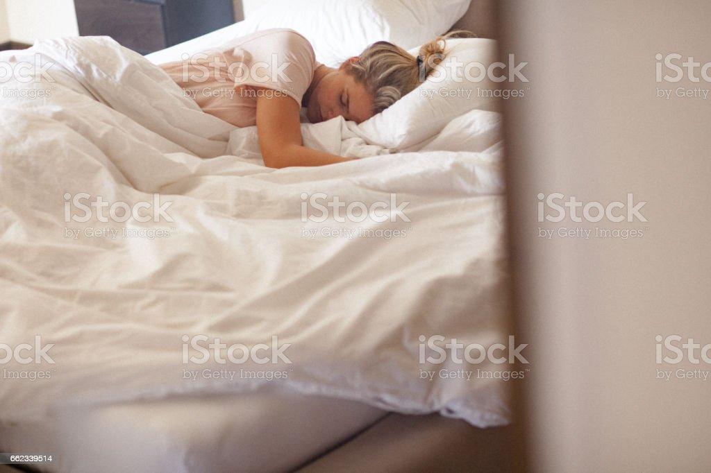 Jeune femme célibataire, dormir dans son lit à la maison le matin - Photo