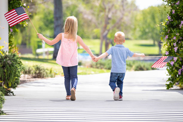 Young Sister and Brother Holding Hands and Waving American Flags At The Park stock photo
