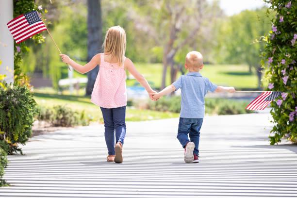Junge Schwester und Bruder Hand in Hand und wehenden amerikanischen Fahnen im Park – Foto