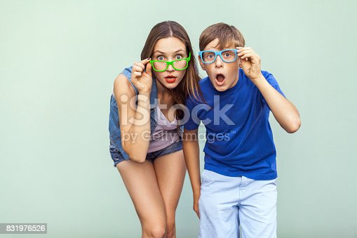 istock Young sister and brother with freckles on their faces, wearing trendy glasses, posing over light green background together. Looking at camera with surprised face. 831976526
