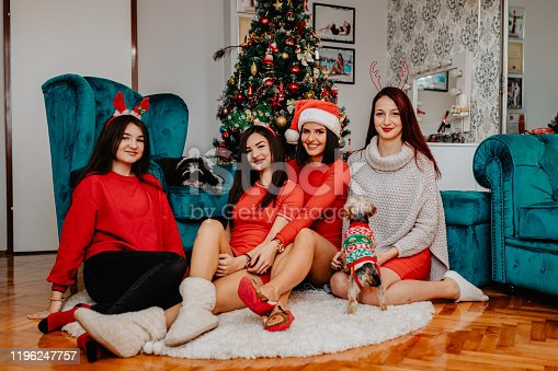 Happy and smiling young sisters and cousins enjoying Christmas holidays with their family Yorkshire terrier dog at home