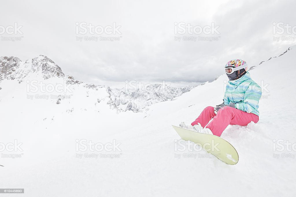 Young sitting woman with snowboard stock photo