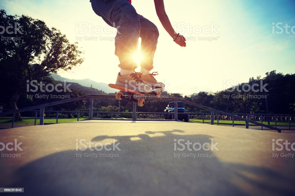 young skateboarder legs practice ollie at skatepark ramp foto stock royalty-free