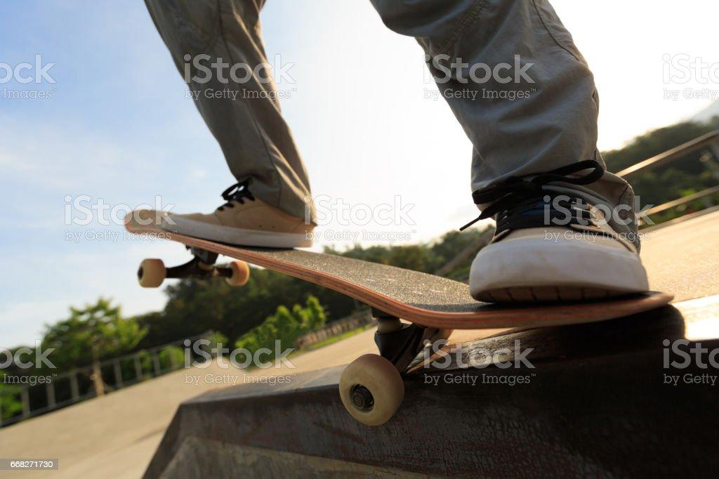 young skateboarder legs riding skateboard at skatepark ramp foto stock royalty-free
