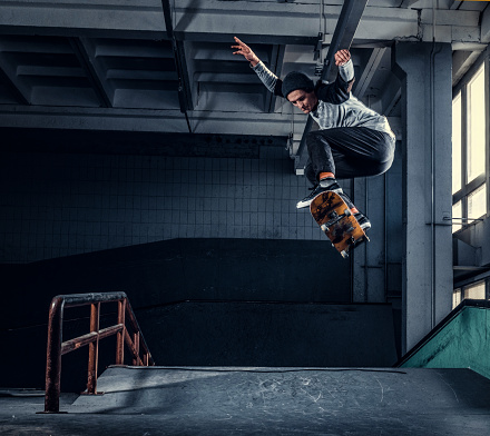 Young skateboarder performing a trick on mini ramp at skate park indoor.
