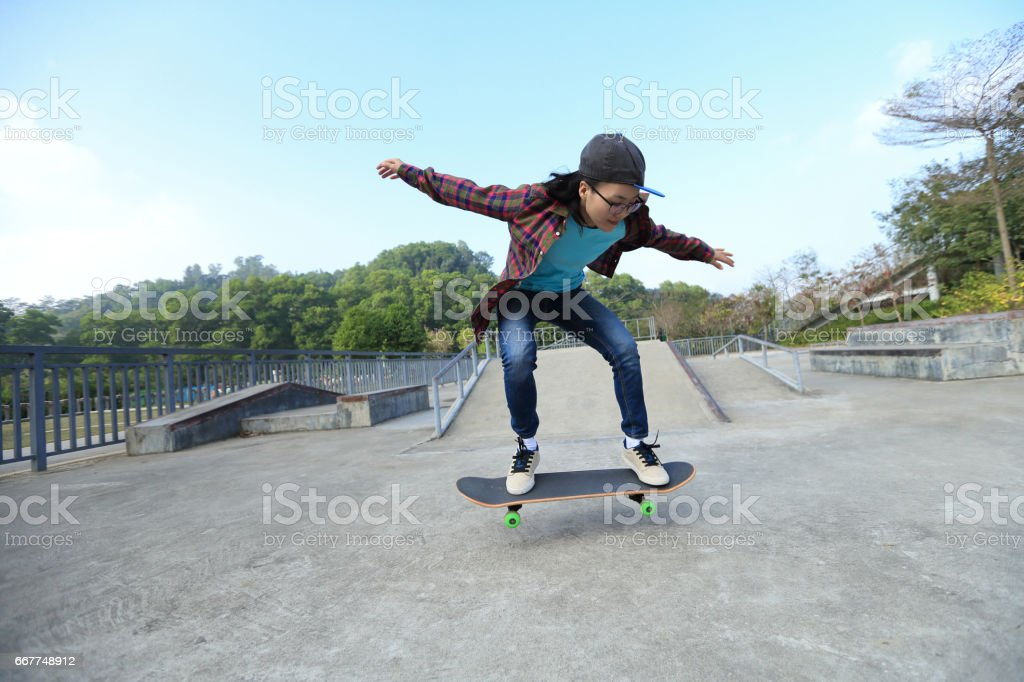 young skateboarder riding skateboard at skatepark stock photo