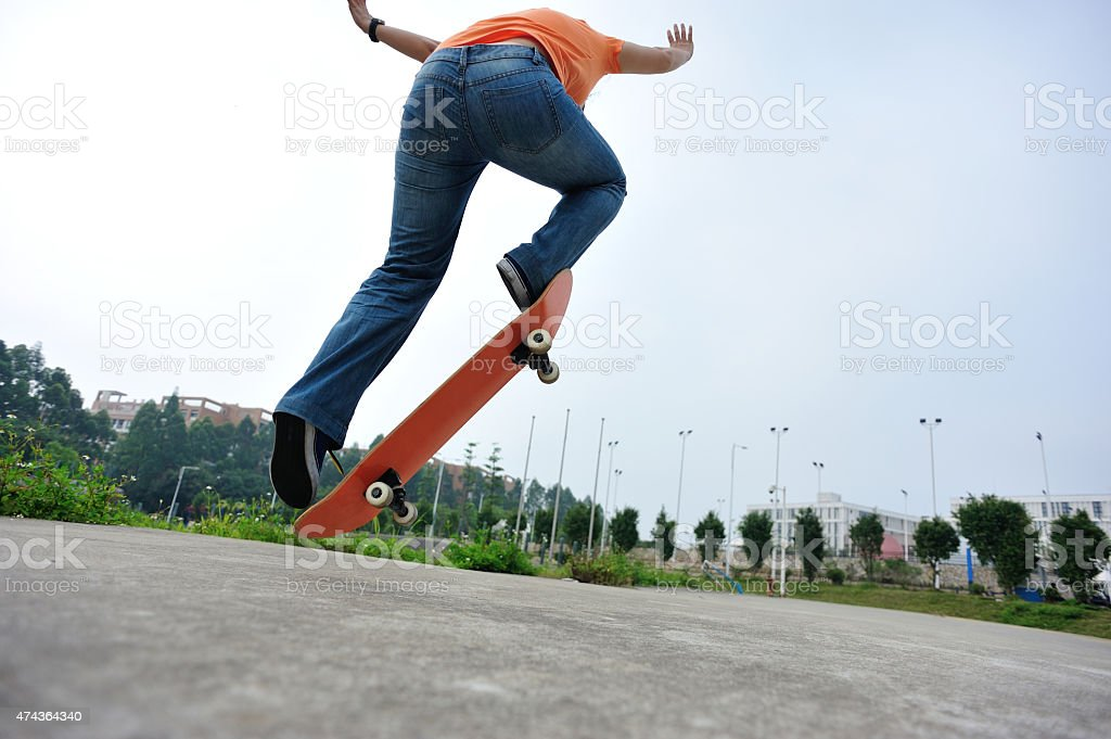 young skateboarder skateboarding outdoor stock photo
