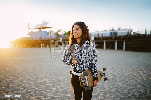 Young mixed Latina woman enjoying the beautiful Santa Monica beach in Los Angeles, California. She is wearing a fashionable spring jacket, going to meet her friends near the beach, holding an old school longboard under her arm.