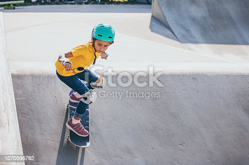 Young Skateboarding Girl Dropping From a Bank in Skatepark.