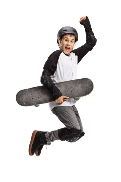 Young skater holding a skateboard and jumping stock photo