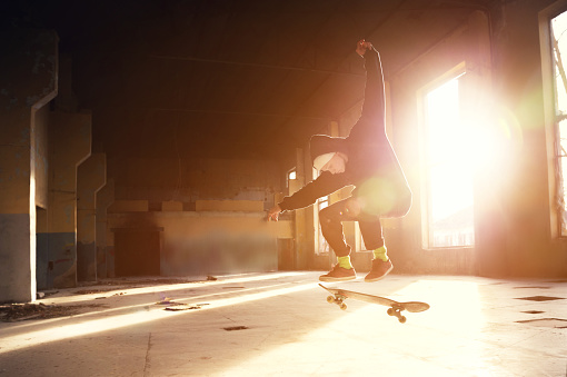 A young skater in a white hat and a black sweatshirt does a trick with a skate jump in an abandoned building in the backlight of the setting sun