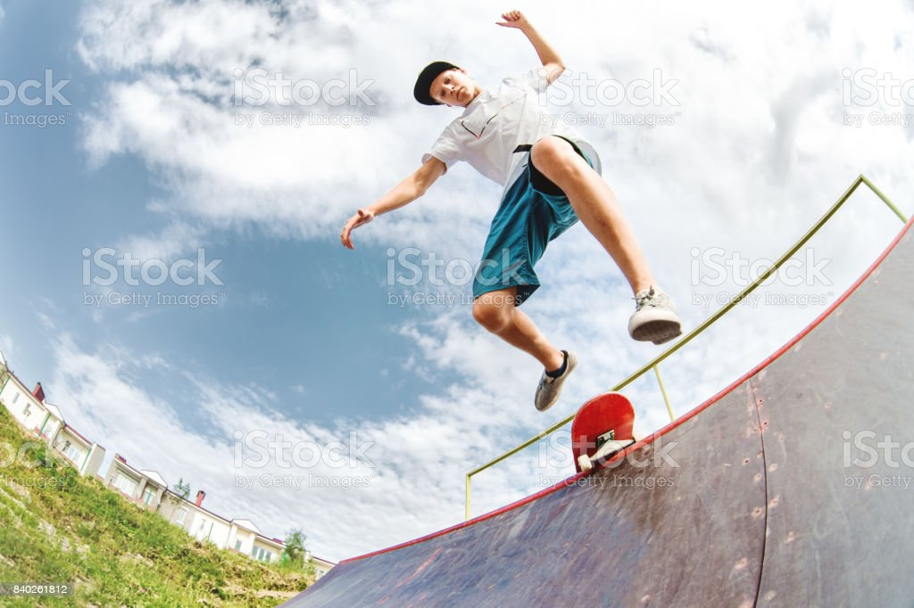 Young skater jumps from ramp down stock photo