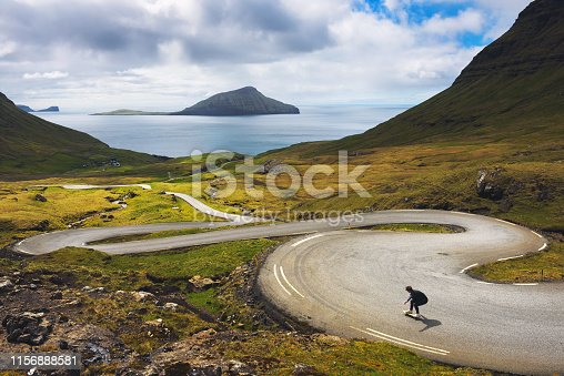 Young skater riding a skateboard on a winding road of Faroe Islands surrounded by beatiful scenery