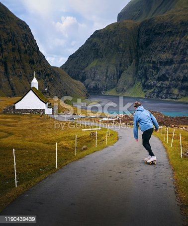 Young skater riding a skateboard on a road in the village of Saksun, Faroe Islands, surrounded by beatiful scenery
