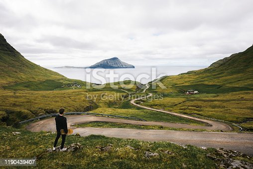 Young skater with his skateboard looks at a winding road on Faroe Islands surrounded by beatiful scenery and Atlantic Ocean in the background