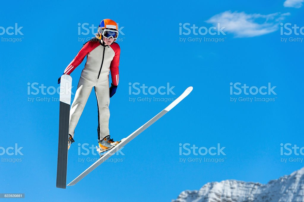 Young Ski Jumper in Mid-air Against the Blue Sky stock photo