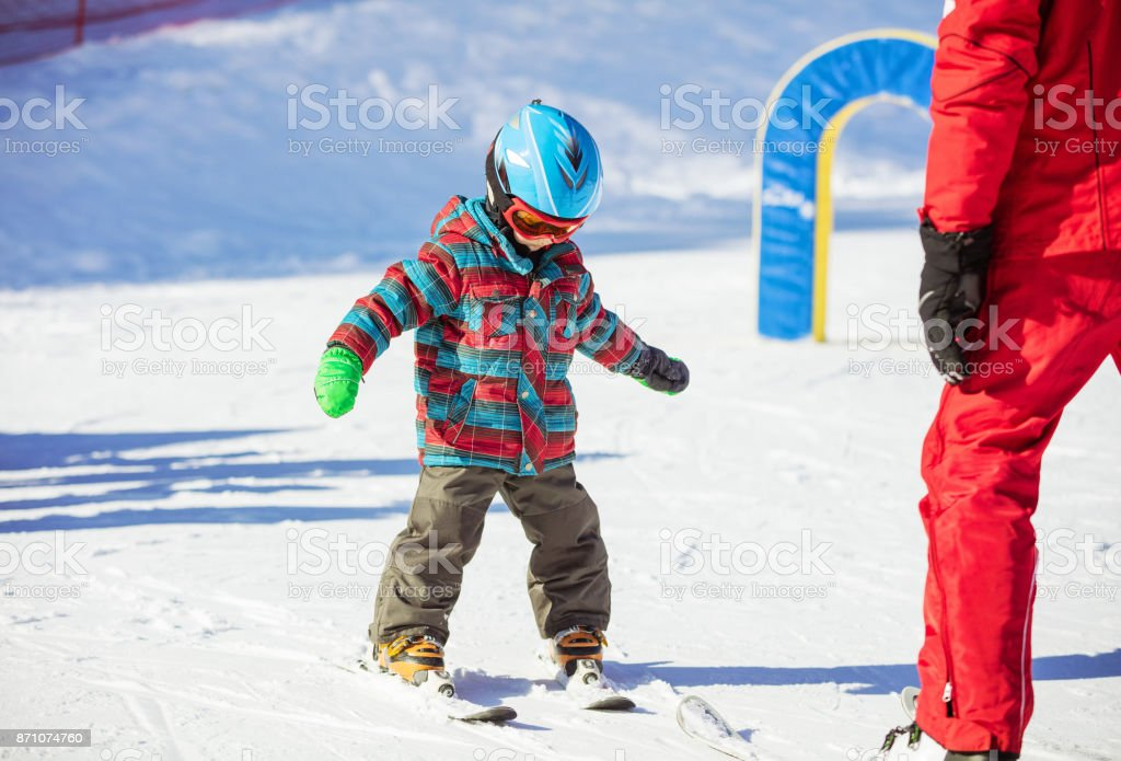 Young skier and ski instructor on slope in beginners' area stock photo