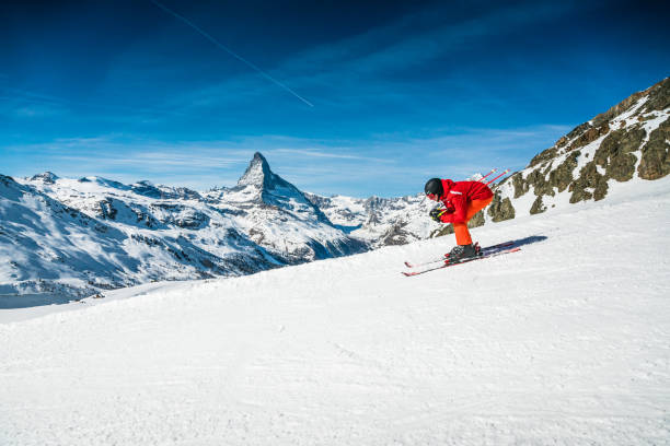 Young skier skiing downhill at Zermatt ski resort, Switzerland Young skier downhill skiing at Zermatt ski resort with Matterhorn mountain in background, Valais canton, Switzerland, in winter morning. Taken by Sony a7R II, 42 Mpix. zermatt stock pictures, royalty-free photos & images