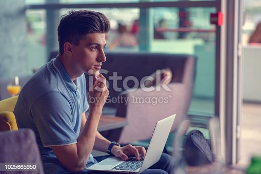 istock Young skilled male freelancer starting working day early in morning drinking coffee to wake up 1025665950