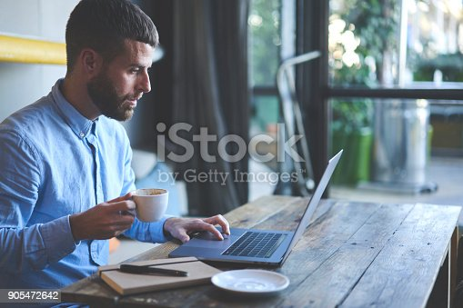 904263506 istock photo Young skilled male freelancer starting working day early in morning drinking coffee to wake up making new design for website with new advertising content using modern laptop computer and wifi 905472642