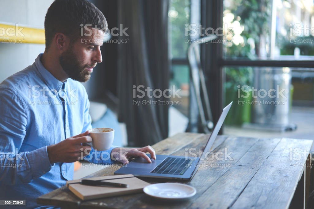 Young skilled male freelancer starting working day early in morning drinking coffee to wake up making new design for website with new advertising content using modern laptop computer and wifi stock photo