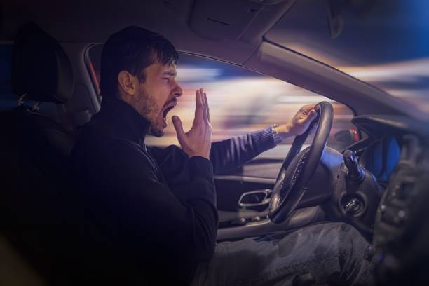 Young sleepy man is yawning and driving car at night. stock photo
