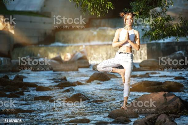 Photo of Young slender girl in white practicing yoga outdoors. Evening meditation and relaxation at the river and waterfall. The Tree position of yoga (Vrikshasana).