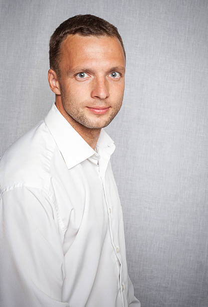 Young slightly smiling man in white shirt stock photo